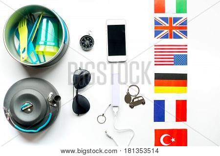 Outfit of traveller with flags and plastic glasses on white table background top view