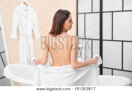 Beautiful young woman with towel going to take a bath at home