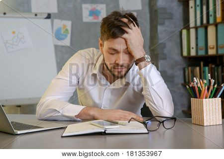 Handsome young man suffering from headache while working in office