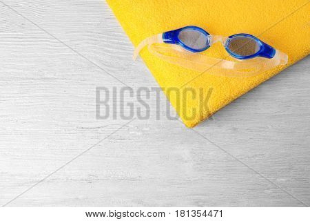 Swimming goggles with towel on wooden background