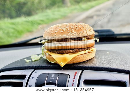 Tasty cheeseburger fast food on the car