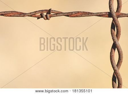 Close-up of a section of  rusty barbed wire fence with a light brown background, with room for text. Can be used as border or background.