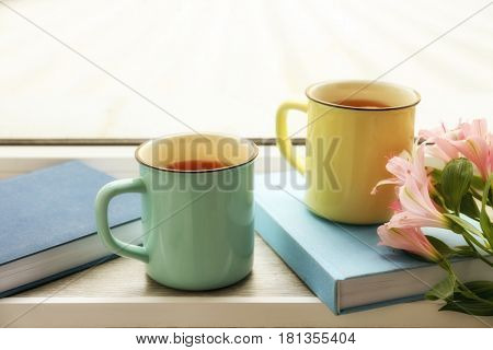 Composition with cups of hot tea on window sill