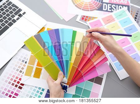 Young designer choosing color of interior while working in office, closeup