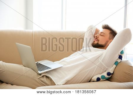 Happy young man lying on sofa with laptop
