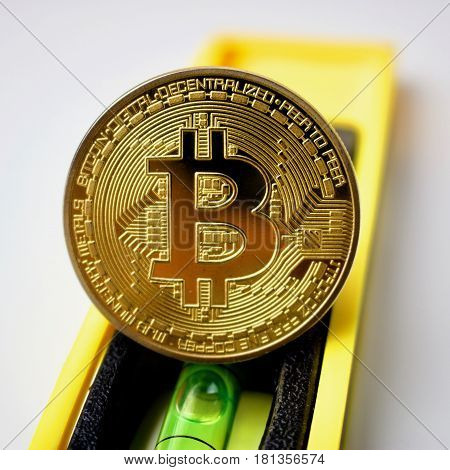 Physical bitcoin gold coin on yellow level