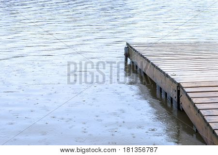 Small wooden dock leading out to a lake wet under heavy rainfall drops splashing into the water camping or weather concept