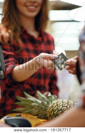 Cropped picture of young woman gives credit card to cashier man at workspace in supermarket.