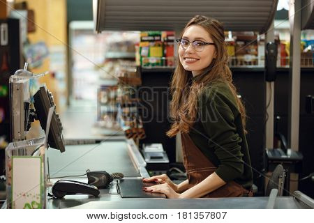 Picture of cheerful cashier woman on workspace in supermarket shop. Looking at camera.