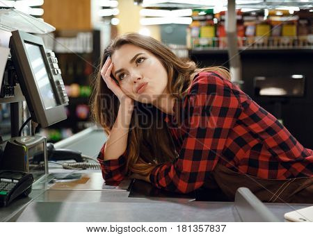 Picture of tired cashier lady lies on workspace in supermarket shop. Looking aside.