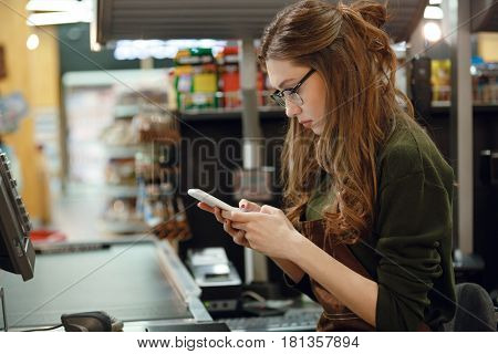 Image of cashier lady on workspace in supermarket shop using mobile phone. Looking aside.