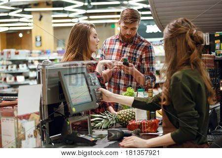 Photo of concentrated young couple standing in supermarket shop near cashier's desk. Looking aside.