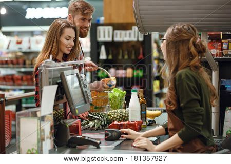Image of happy young loving couple standing in supermarket shop near cashier's desk. Looking aside.