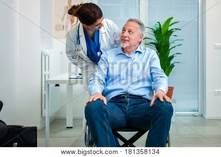 Female doctor talking to a patient on a wheelchair