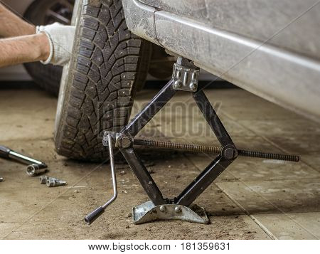 Male hands wrapped the screw in the wheel of the car. Replacement rear wheel vehicle mechanic in the garage.