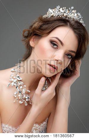 A portrait of elegant girl is in fashion style. Wedding decoration. On a grey background