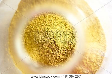 Yellow cosmetic cleansing clay for face and body. Healing Clay is a natural product. Dry cosmetic clay on a wooden background. Selective focus