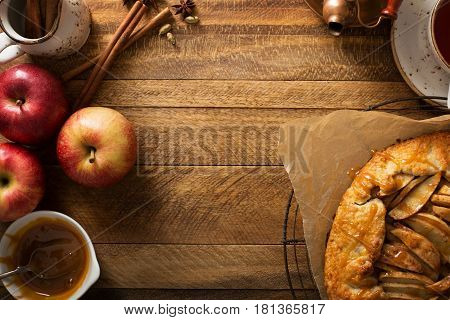 Apple and salted caramel rustic galette, free form pie overhead shot with copy space