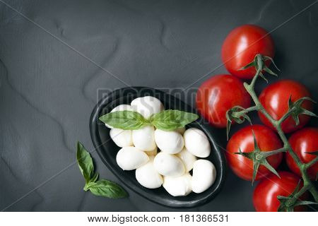Food background.  Top view of slate with baby mozzarella balls with vine tomatoes and basil.