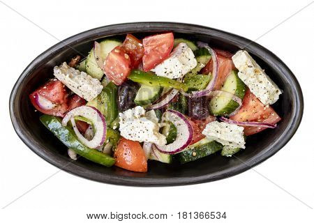 Greek salad in rustic black bowl, top view, isolated on white.