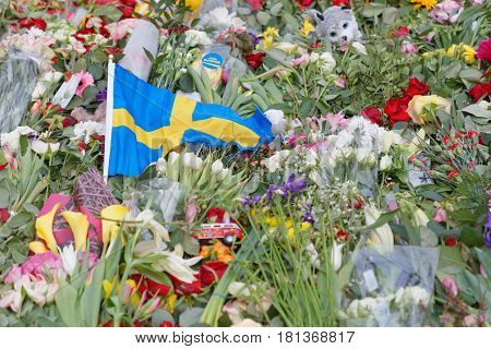 STOCKHOLM SWEDEN - APR 12 2017: Flowers and swedish flag from people paying respect to the victims in the terror attack in Stockholm April 07 2017. April 13 2017 in Stockholm Sweden