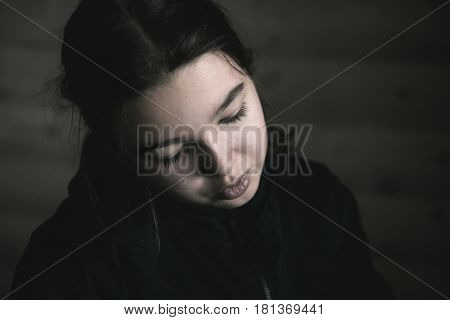 Portrait of a pensive dark-haired teenager girl in a dark room