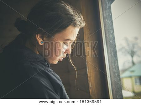 Portrait of a pensive teenager girl by the window. LOMO effect