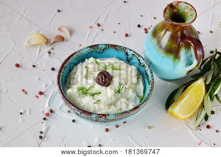 Homemade Greek traditional sauce tzatziki with cucumber garlic yogurt olive oil and lemon in a traditional colored bowl on a white background. Healthy eating concept. Mediterranean lifestyle