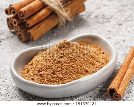 Close up view of ground cinnamon in trendy plate and cinnamon sticks on gray cement background