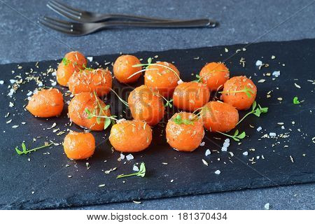 Honey glazed baby carrots with sea salt and thyme in a metal bowl on a grey abstract background. Healthy eating concept. Fastening food. Healthy meal