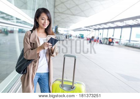 Travel woman using cellphone with luggage