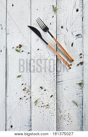 Wood Fork and Knife with Green Herbs, Salt and Pepper on White Wood Background. Flat Lay