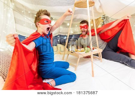 Father And Son In Superhero Costumes Having Fun Together In Blanket Fort