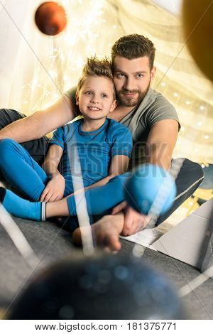 Father And Son Sitting Together In Blanket Fort With Solar System Model On Foreground