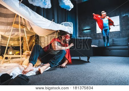 Father And Son In Red Superhero Costumes Playing At Home