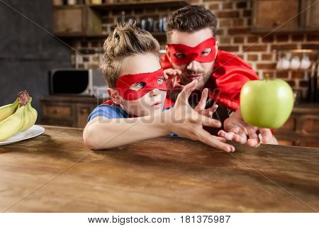 Father And Son In Red Superhero Costumes Playing With Apple