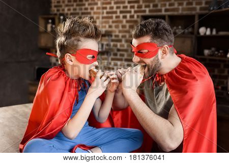 Father And Son In Red Superhero Costumes Eating Sandwiches At Home