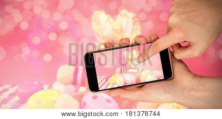 Various Easter eggs with soft toy against hands touching smart phone