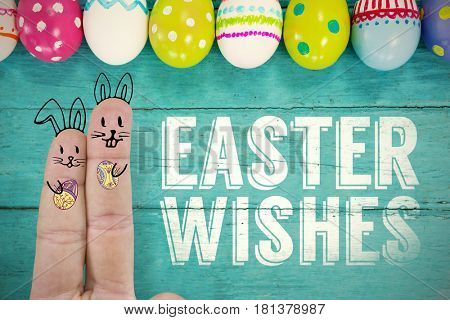 Fingers representing Easter bunny against various easter eggs arranged on wooden surface