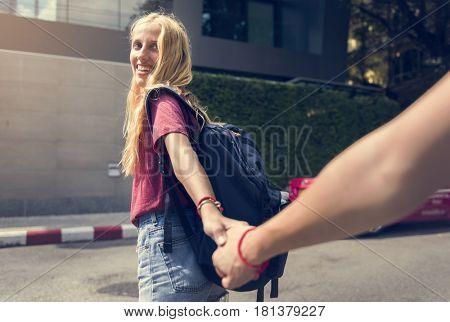 Woman holding boyfriend's hand traveling