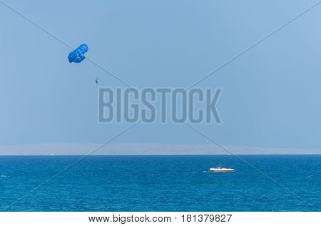 Idyllic Blue Sea With Motor Boat And Parachute Parasailing