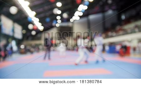 Female karatekas fight on karate competitions, de-focused sport background, wide angle