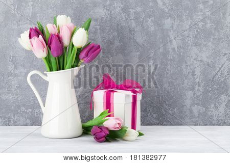 Colorful tulips bouquet and gift box in front of stone wall with space for your greetings