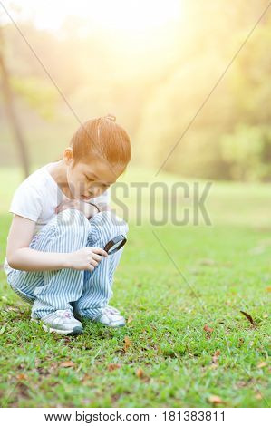 Portrait of Asian child with magnifier glass exploring nature at park, copy space at side. Little girl having fun outdoors. Morning sun flare background.