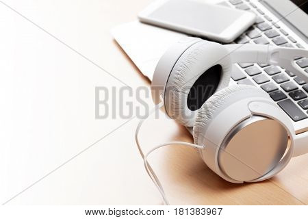 Headphones over laptop on wooden desk table. Music concept. View with copy space