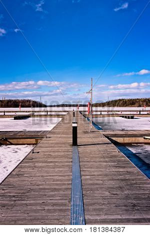 A wooden pier on a frozen lake in Lappeenranta Finland. In the summertime the pier is full of small motor boats and sailboats.
