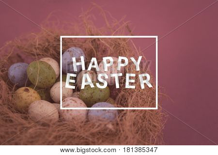 Easter greeting against colorful chocolate easter eggs in the nest