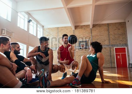 Photo of handsome basketball players sitting on the court and having fun.