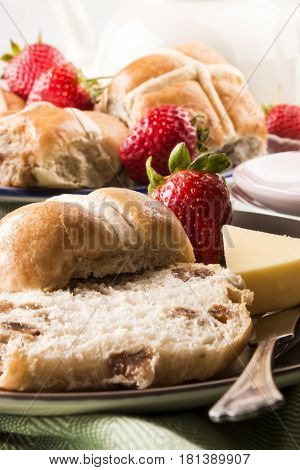 hot cross buns and sweet strawberries and butter on a plate