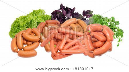 Pile of the uncooked various thick wieners bound by twine and thin frankfurters on the background of leaves of lettuce and bundles of the purple basil and parsley on a light background